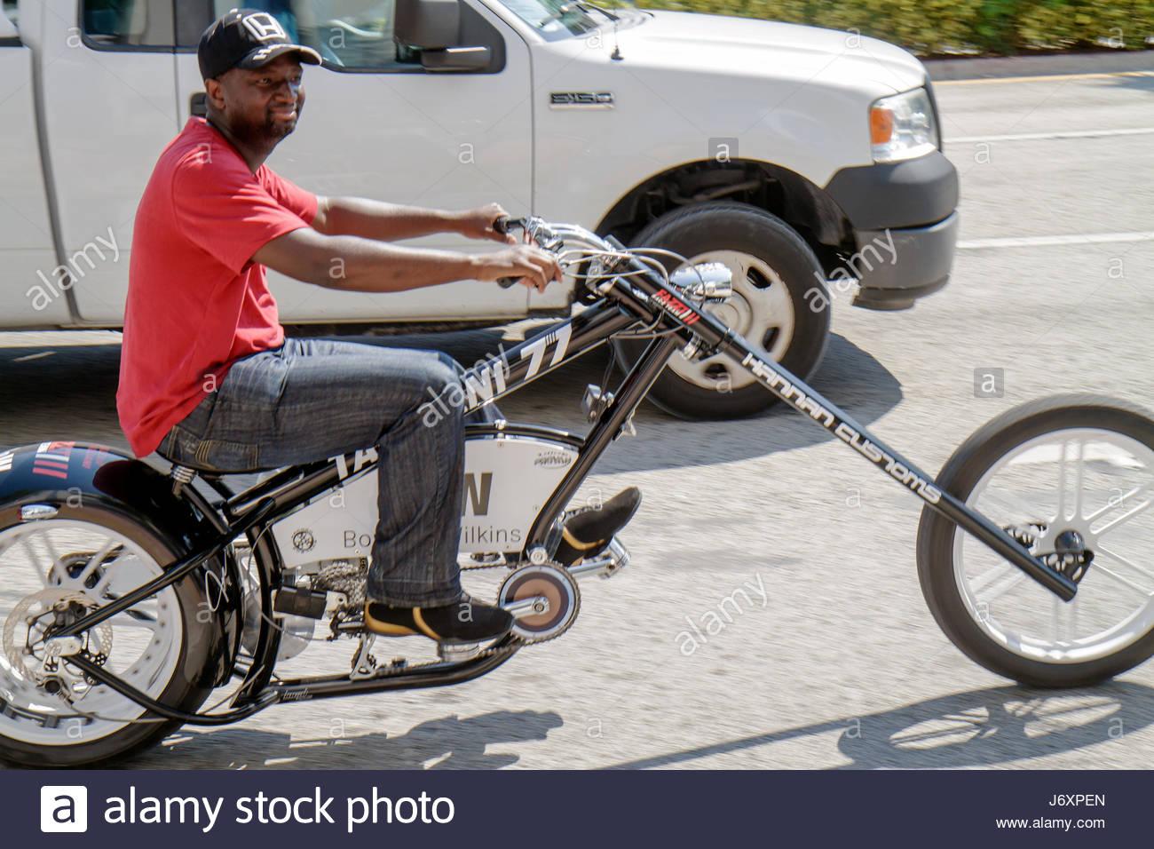 Miami Beach Florida 5th Fifth Street customized bicycle imitation motorcycle chopper pedal Black man - Stock Image