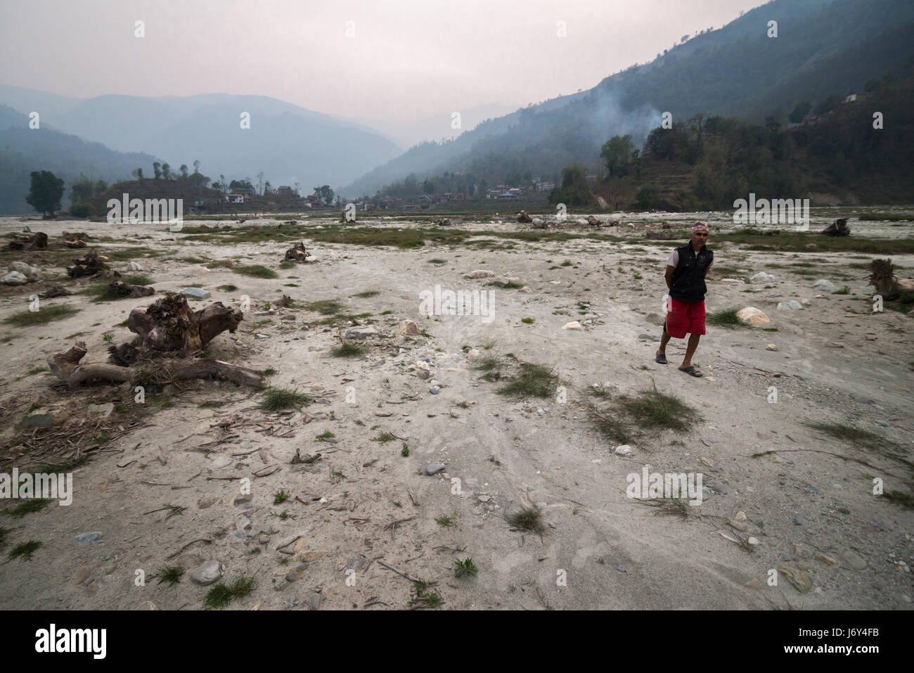 A man walks through a wide floodplain in Khani Khahare near Kaski and Nuwakot, Nepal. - Stock Image