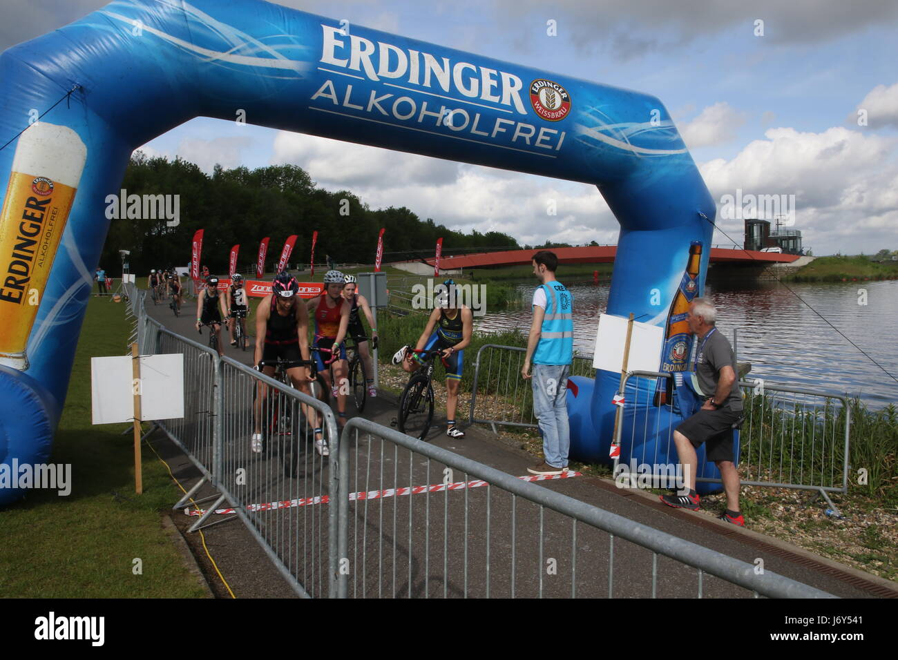 Triathletes reach the end of the cycle leg of a triathlon watched by race officials - Stock Image