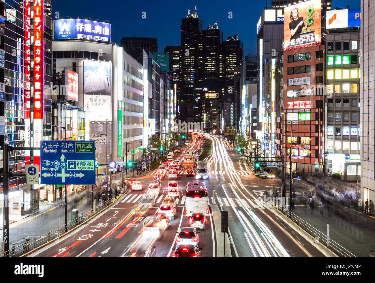 TOKYO - MAY 2, 2017: Traffic, captured with blurred motion, rushes through the busy streets of  the Shinjuku business - Stock Image