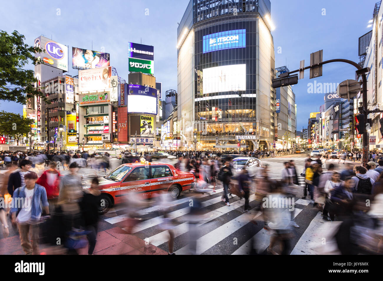 TOKYO - MAY 3, 2017: A taxi is stuck among the crowd crossing the famous Shibuya crossing at night in Tokyo, Japan - Stock Image