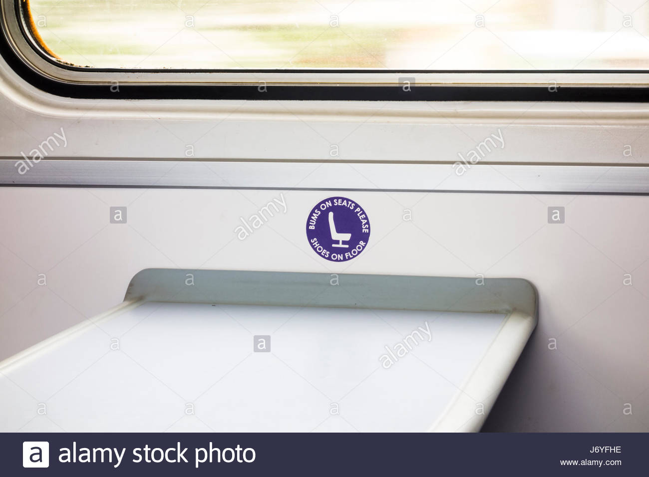 Sign on a Northern Rail train - Bums on Seats please, Shoes on Floor - Stock Image