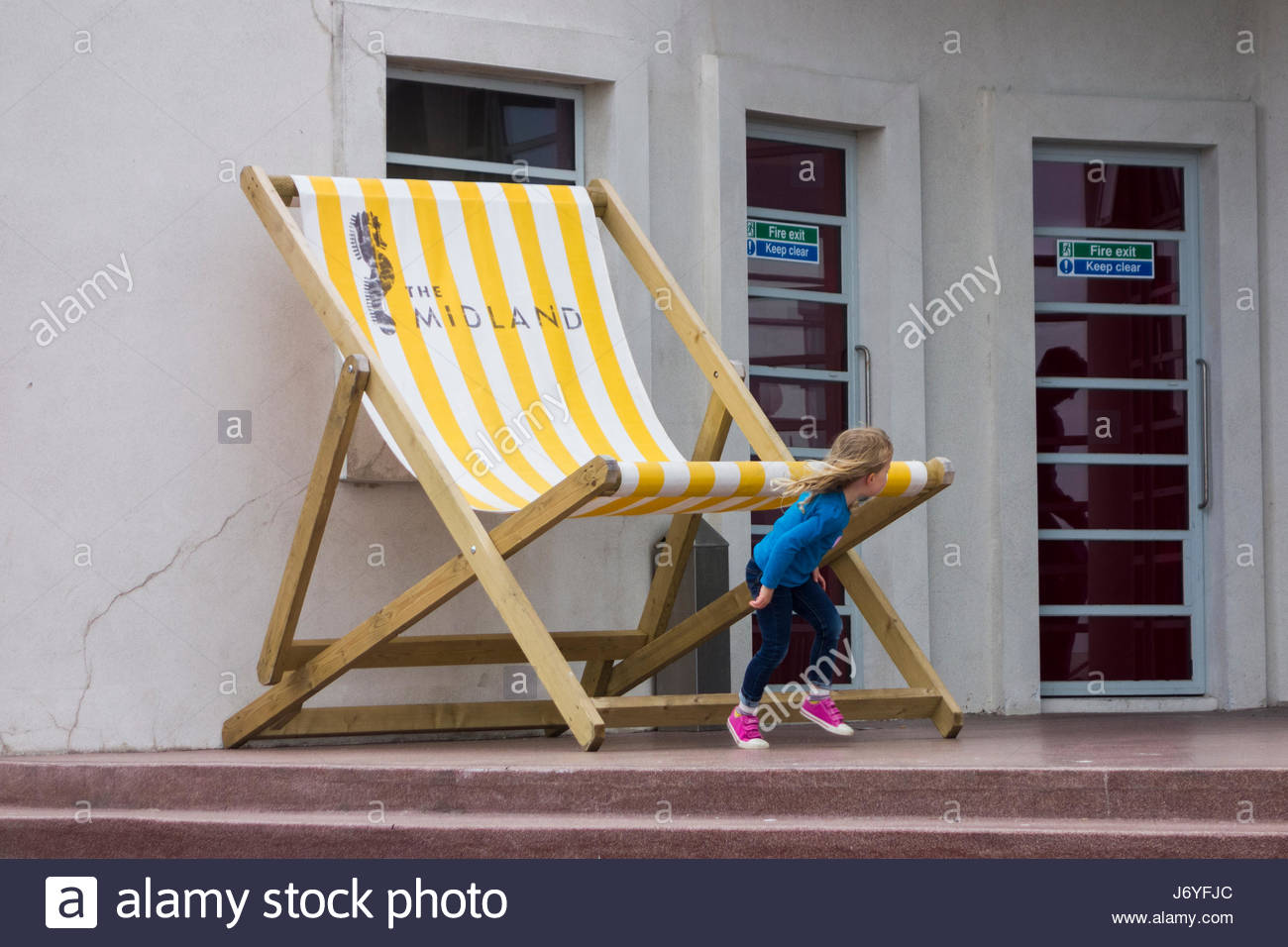 A young child plays next to the oversize deckchair at the Midland Hotel, Morecambe - Stock Image