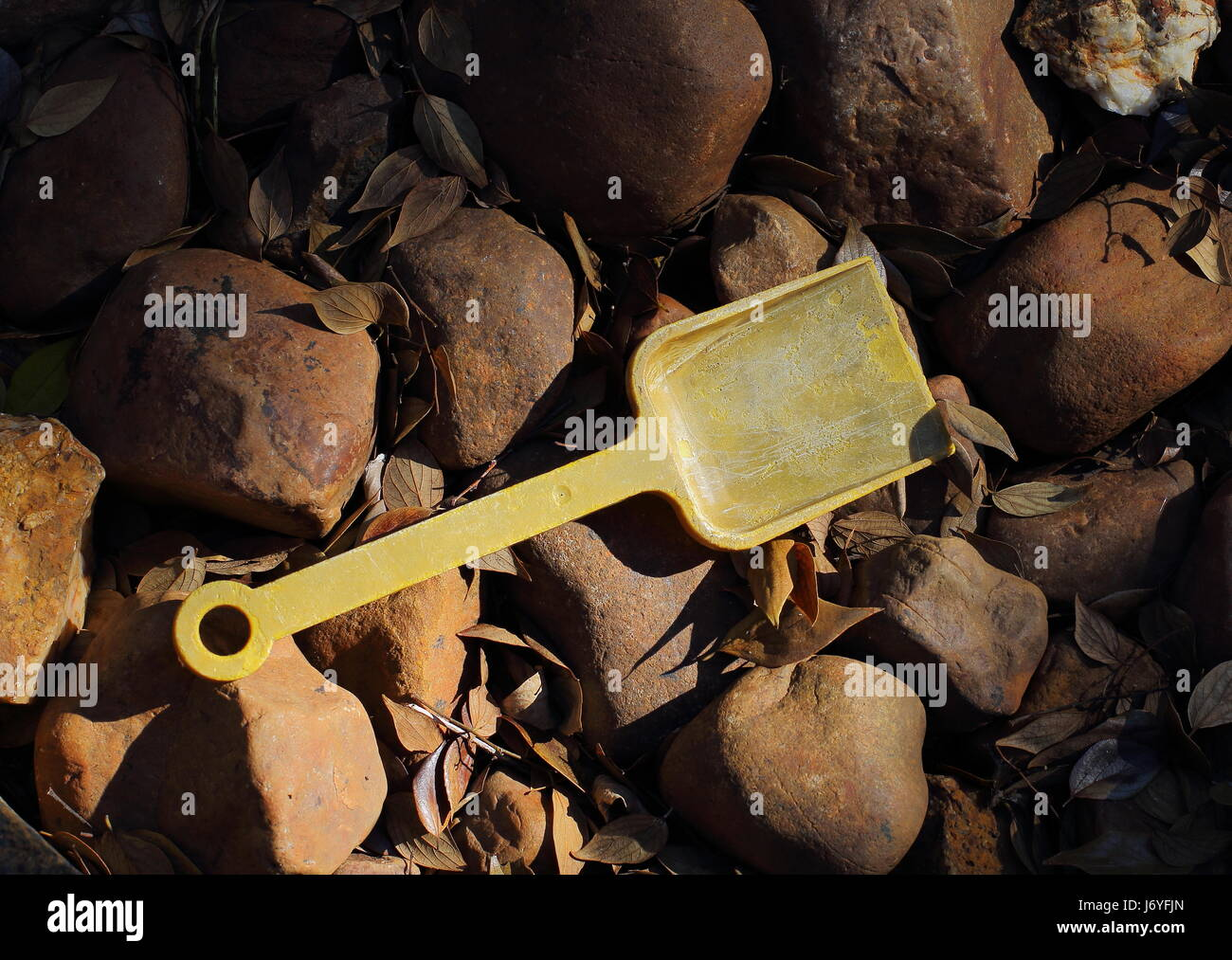 An abandoned and faded yellow child's toy spade Stock Photo