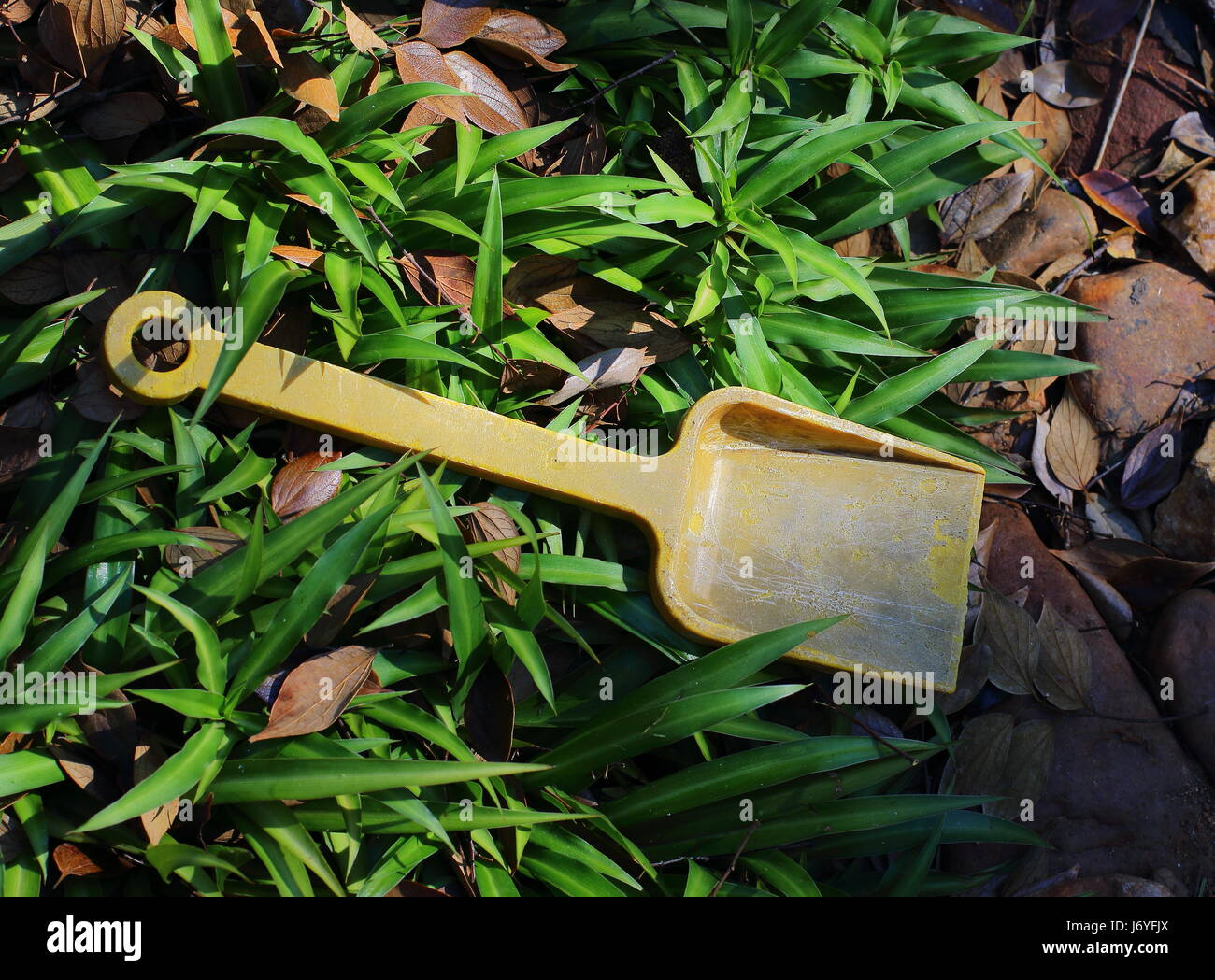 An abandoned and faded yellow child's toy spade - Stock Image