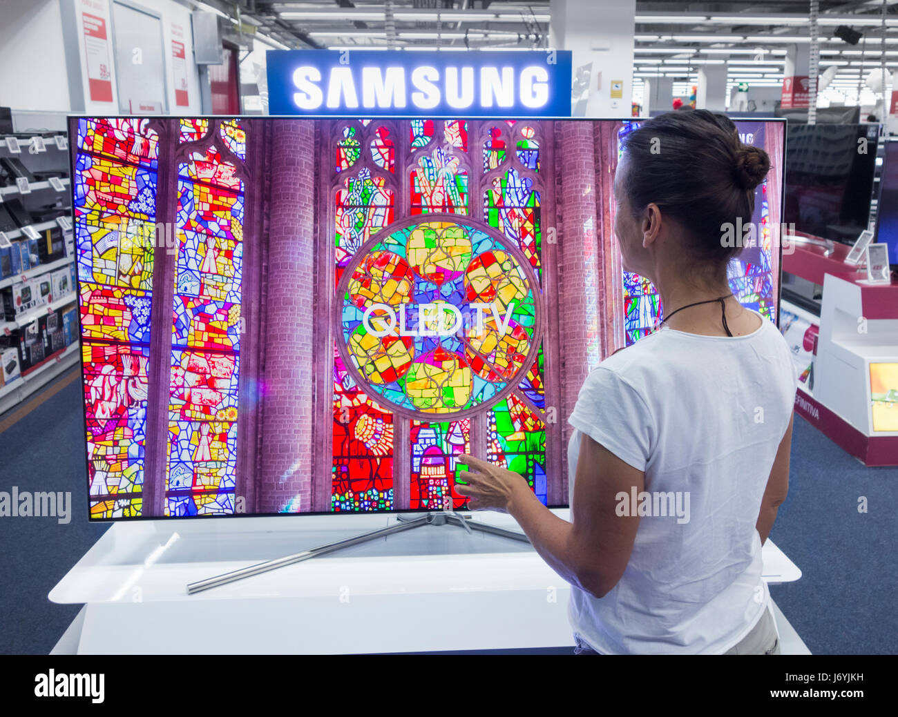 Woman looking at Samsung QLED TV in electrical store. - Stock Image