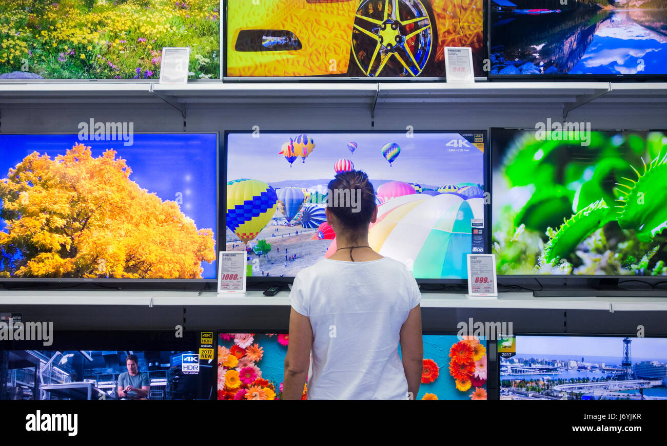 Woman looking TV screens in electrical store. - Stock Image