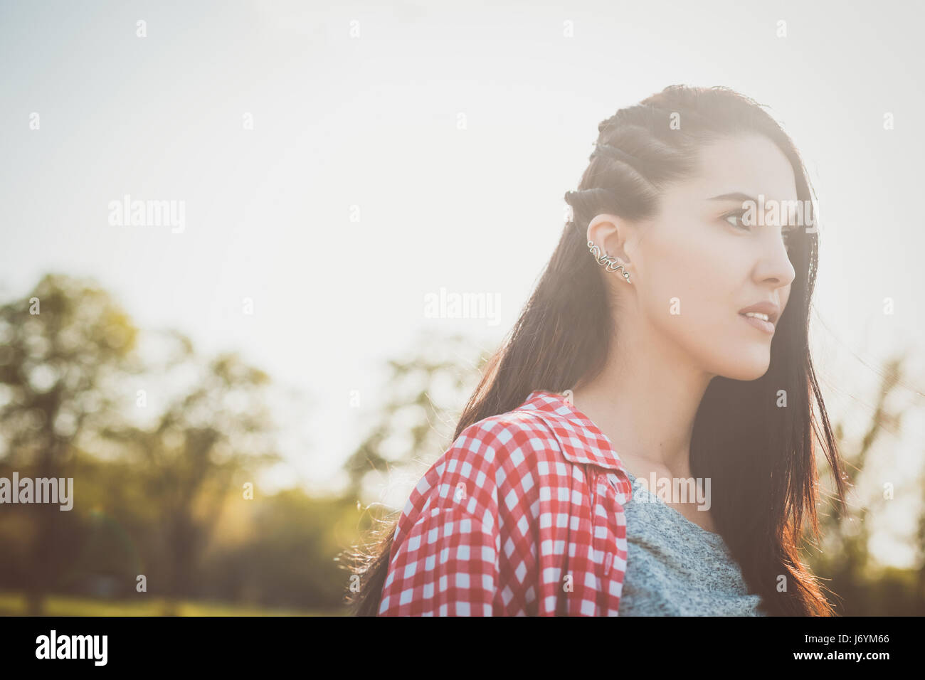 close up portrait of pretty hipster girl outdoors. looking in the distance. concept of freedom purposeful teenager - Stock Image