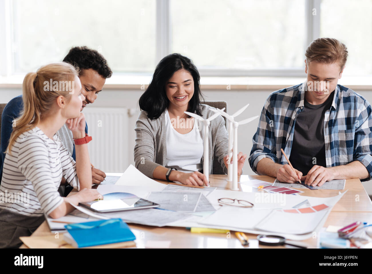 Joyful positive team of engineers working together - Stock Image