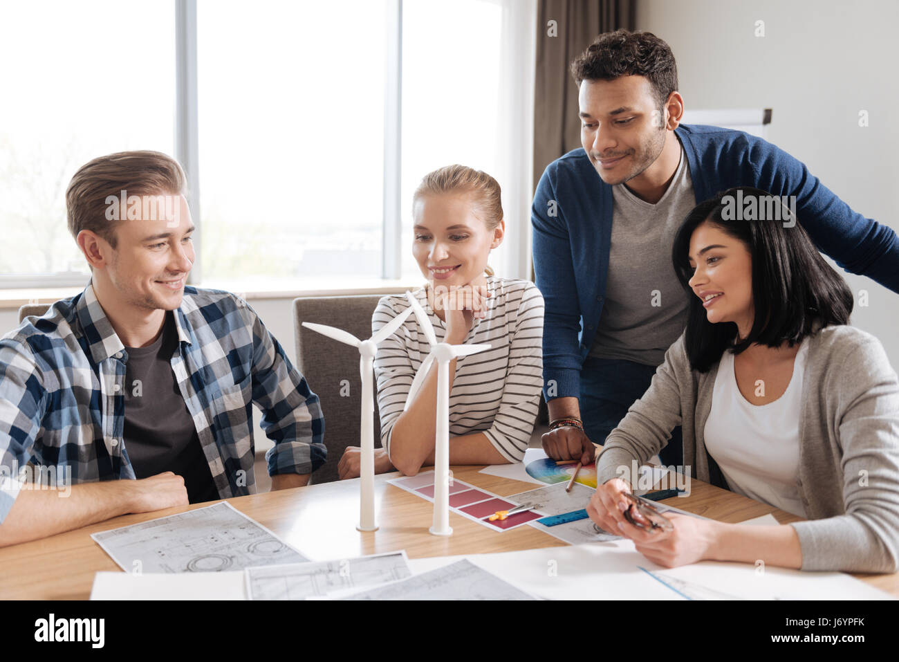 Positive nice team of engineers trying to save the energy - Stock Image