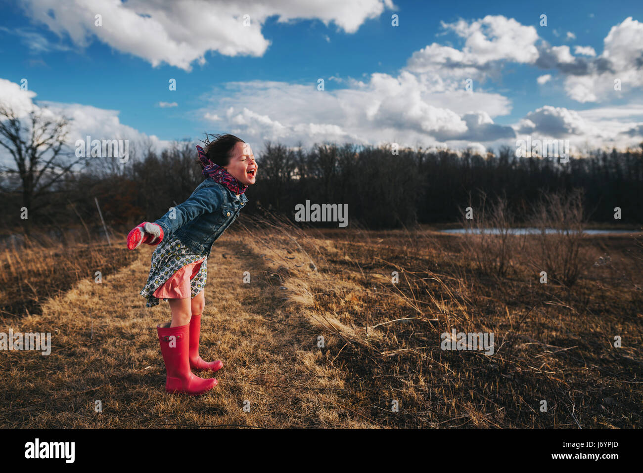 Girl with arms outstretched  shouting into the wind Stock Photo