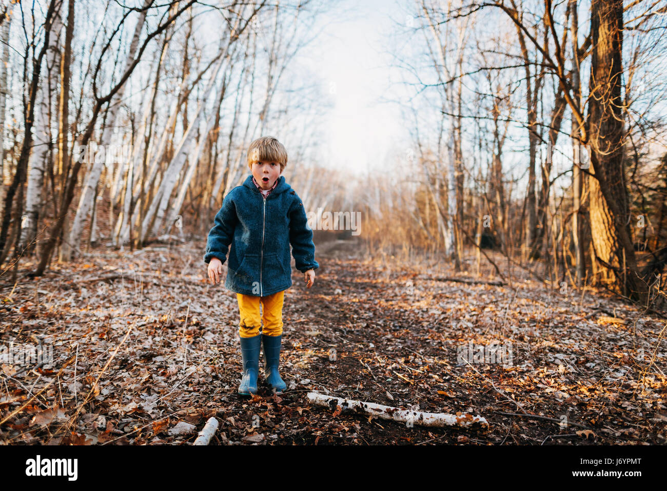 Boy standing in forest pulling funny faces - Stock Image