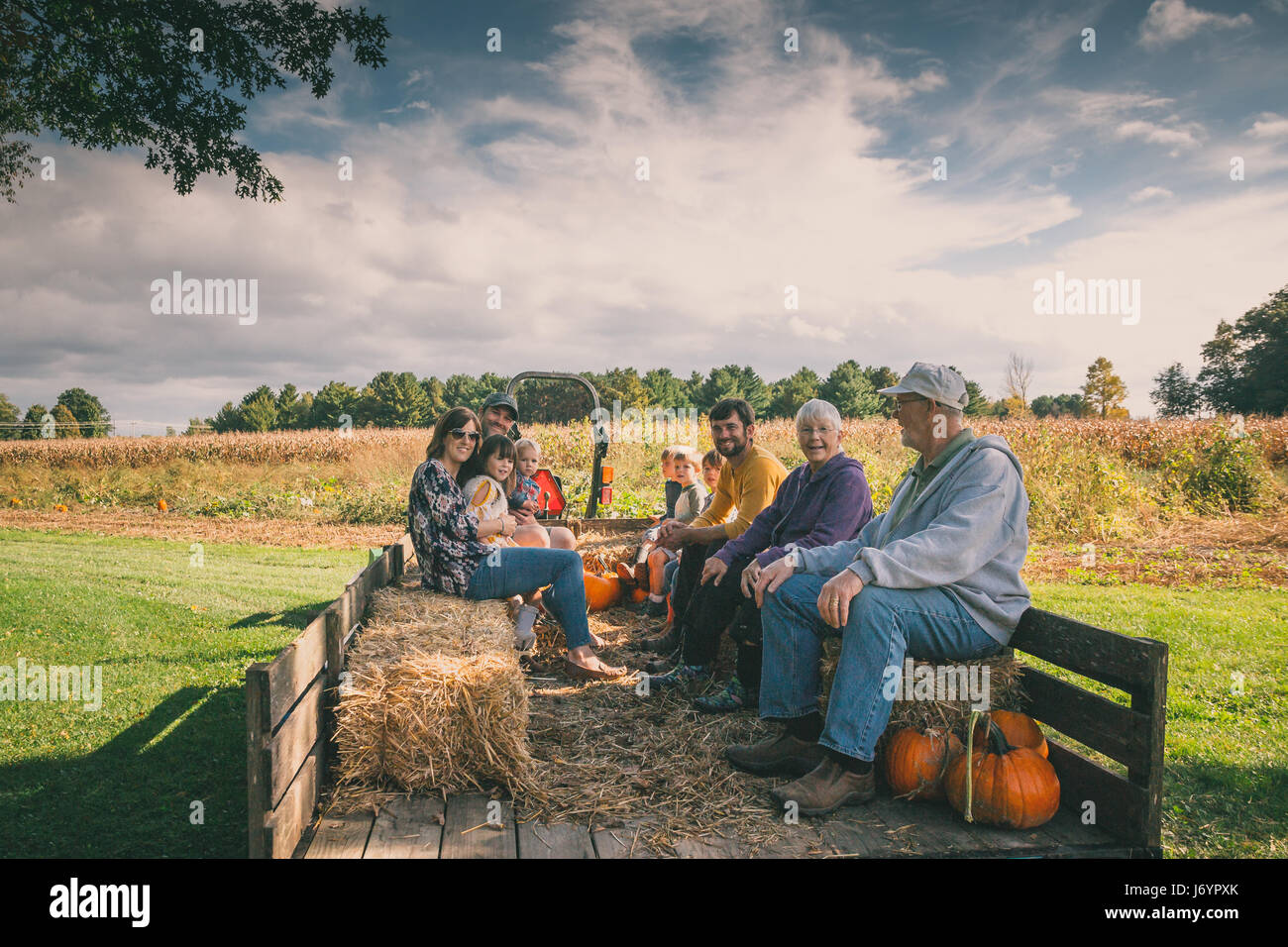 Multi-generation family sitting in a wagon at a pumpkin patch - Stock Image