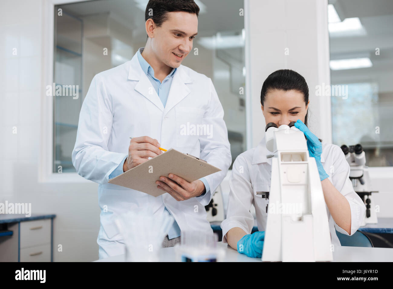 Positive delighted lab assistant holding folder - Stock Image