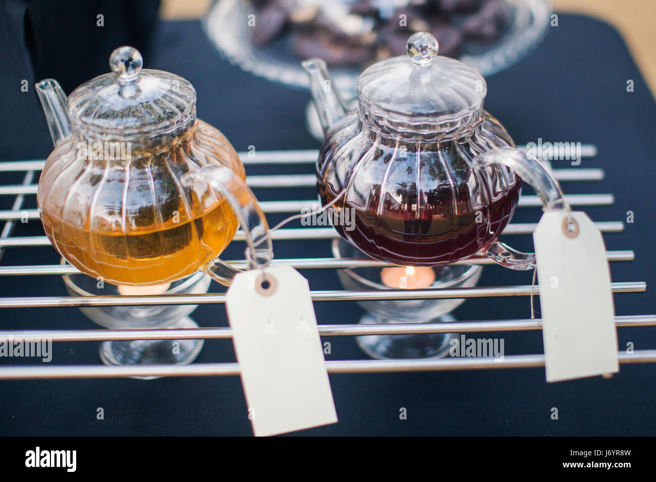 Two teapots on teapot warmers - Stock Image