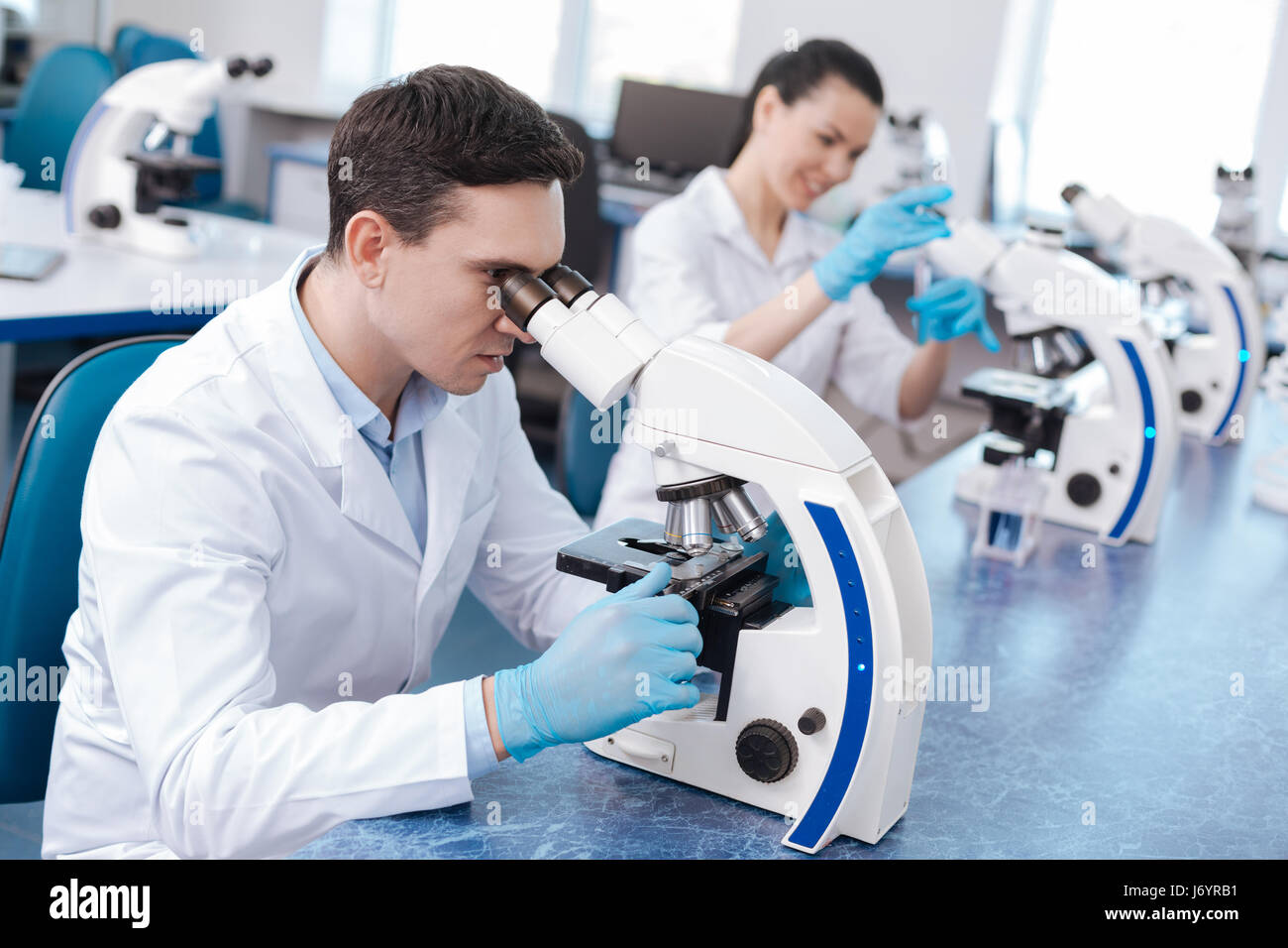 Very attentive lab assistant working with microscope - Stock Image