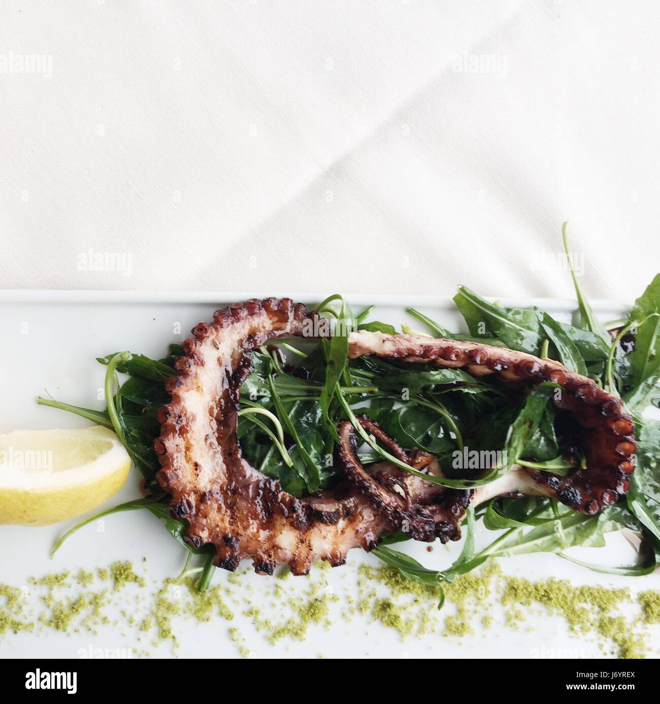 Grilled octopus with lemon and rocket Stock Photo