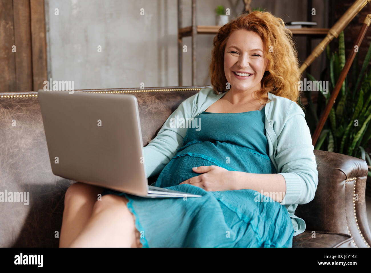 Radiant expectant mother working on laptop on sofa - Stock Image