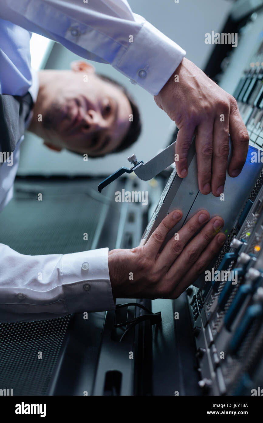 Serious nice man installing a blade server - Stock Image