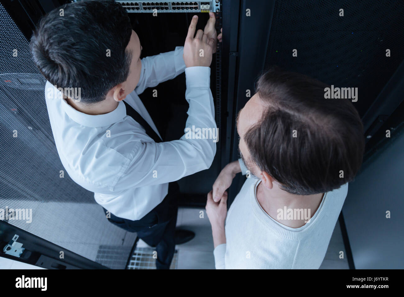 Top view of male technicians deciding what to do - Stock Image
