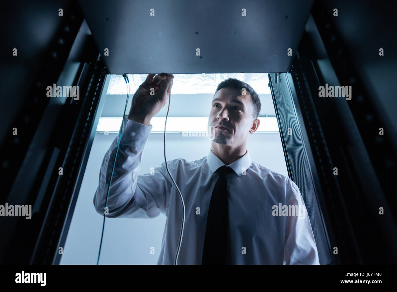 Nice pleasant man putting Ethernet cable into the rack server - Stock Image