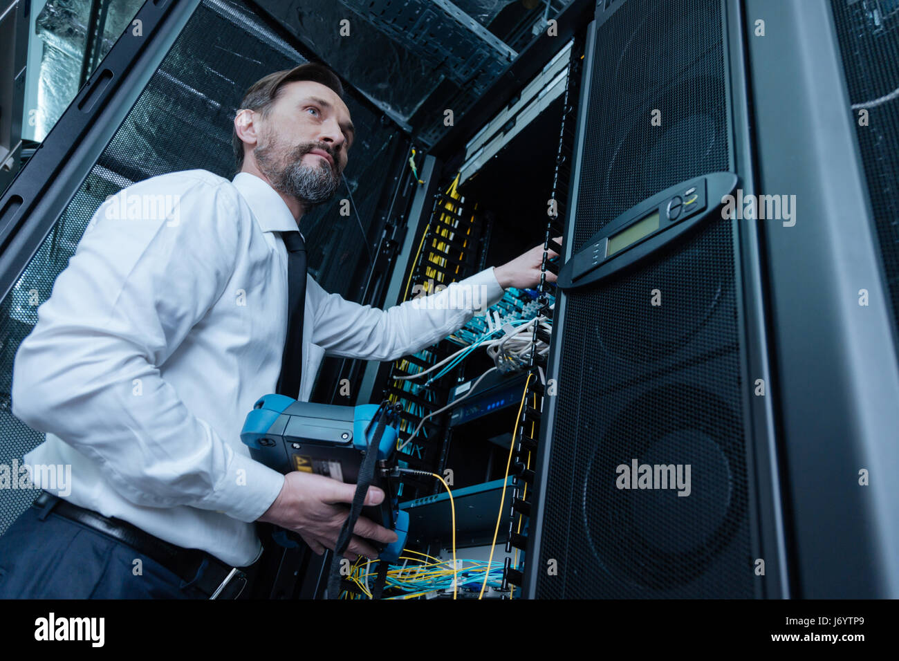Handsome professional technician repairing the network server - Stock Image