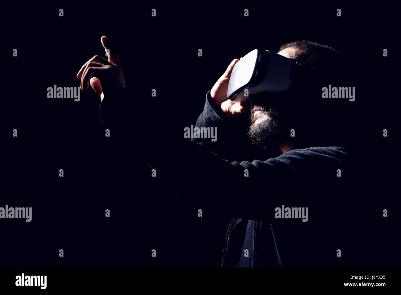 Young hipster bearded man wearing virtual reality goggles. Black background studio VR concept - Stock Image