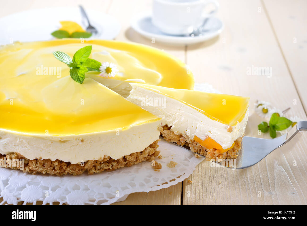 Fresh cheesecake with mango fruit and glaze, the flan case made of cookie crumbs - Stock Image