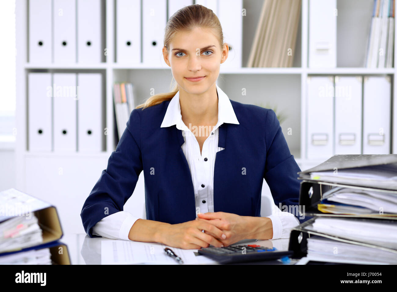 Modern business woman or confident female accountant in office - Stock Image