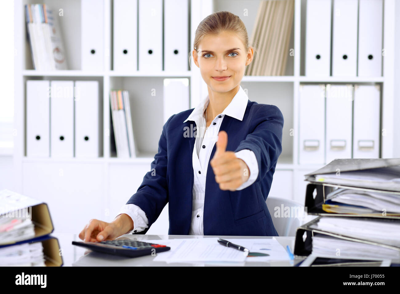 Modern business woman or confident female accountant, thumb up - Stock Image