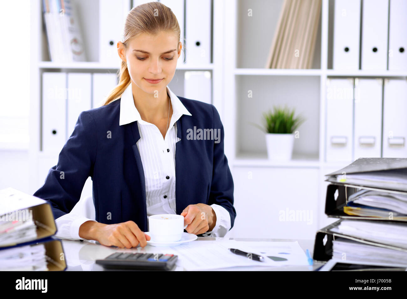 Happy business woman or female accountant having some minutes for coffee and pleasure at working place - Stock Image