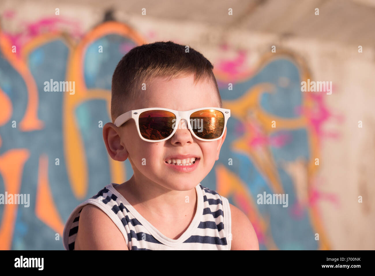 funny small kid wearing sunglasses with sea sunset