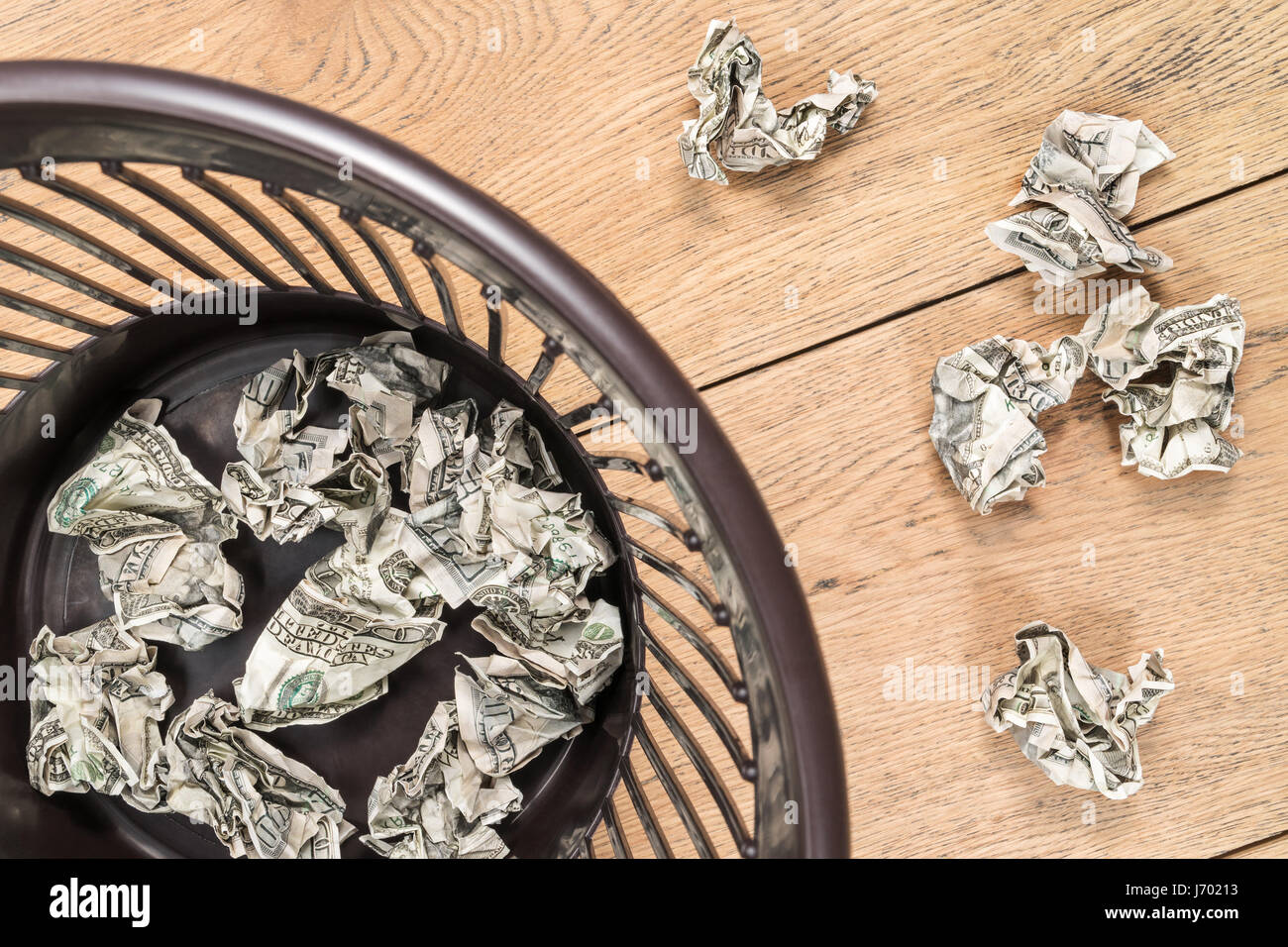 Crumpled money in trash - Stock Image