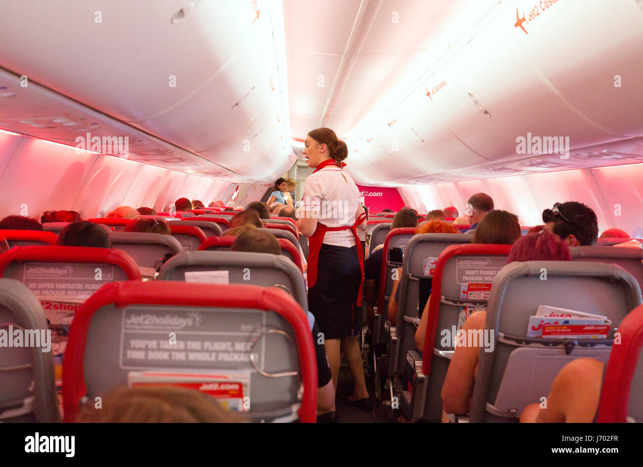 Jet2 airline flight attendant working in the airplane cabin, on a Boeing 737-800 flight from Lanzarote to UK - Stock Image