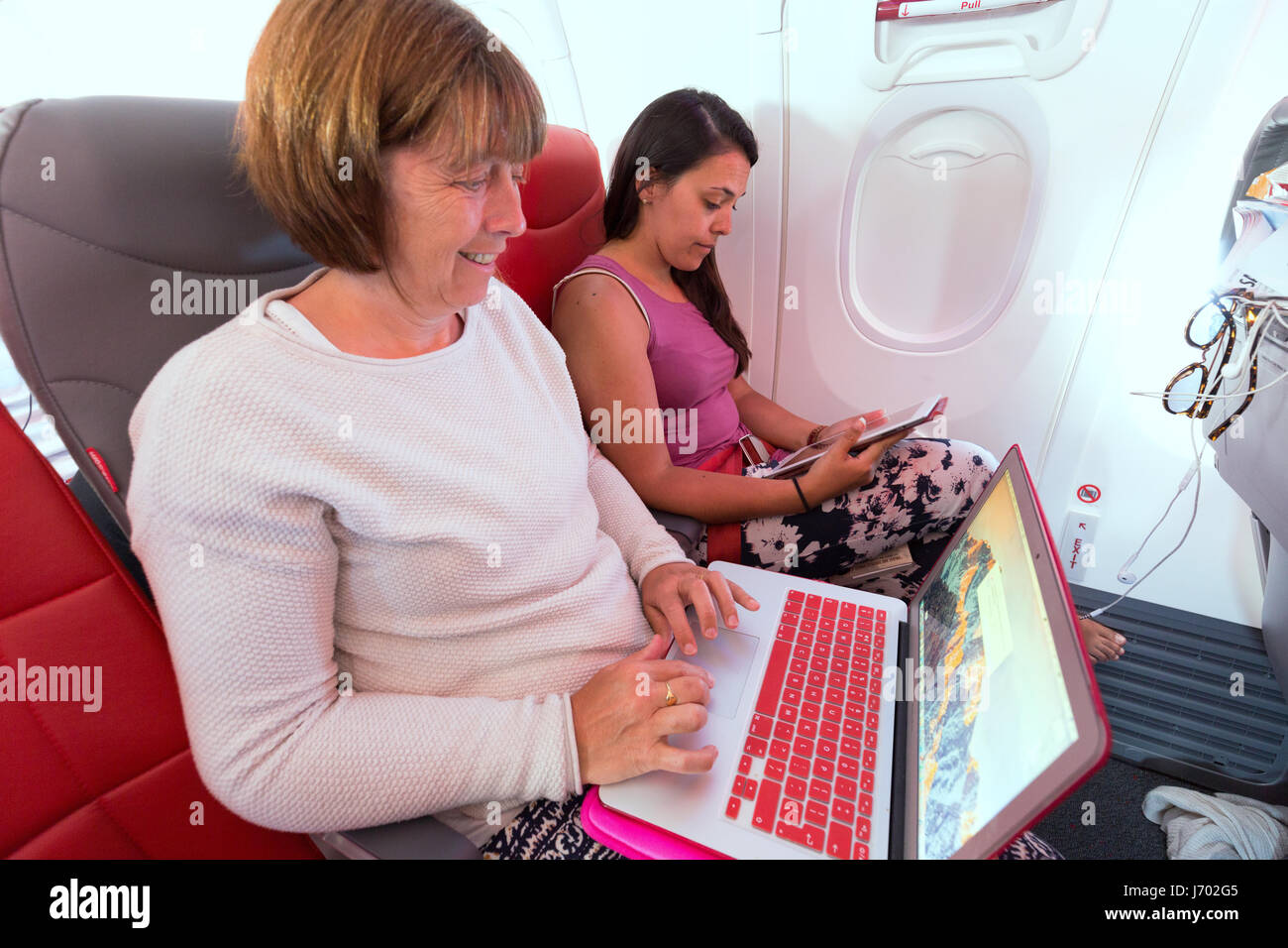 Plane passengers in the airplane cabin using laptop computer and Pad, or tablet computers; in flight - Stock Image