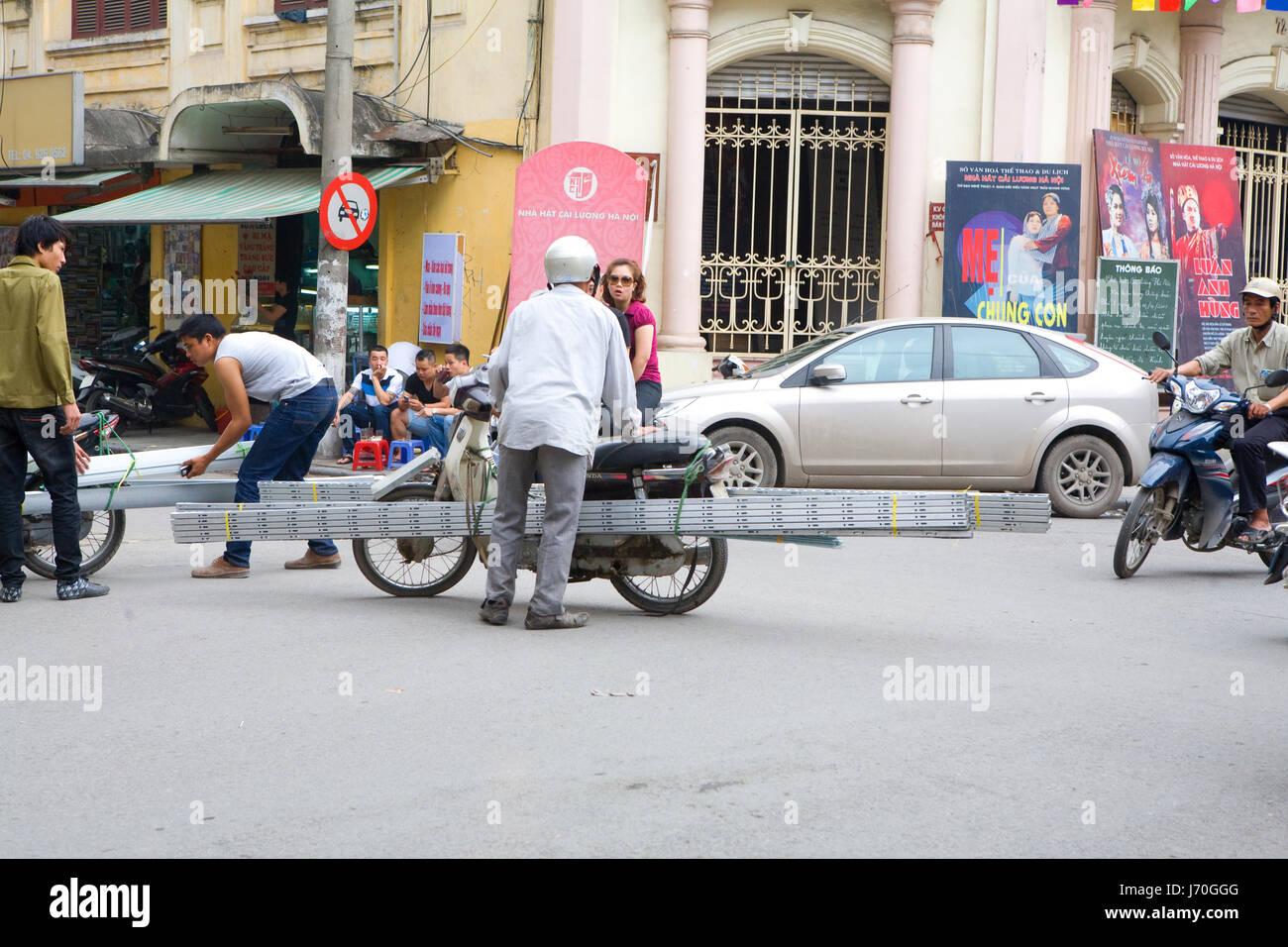 Urban scene with loaded motorbikes in Hanoi, Vietnam - Stock Image