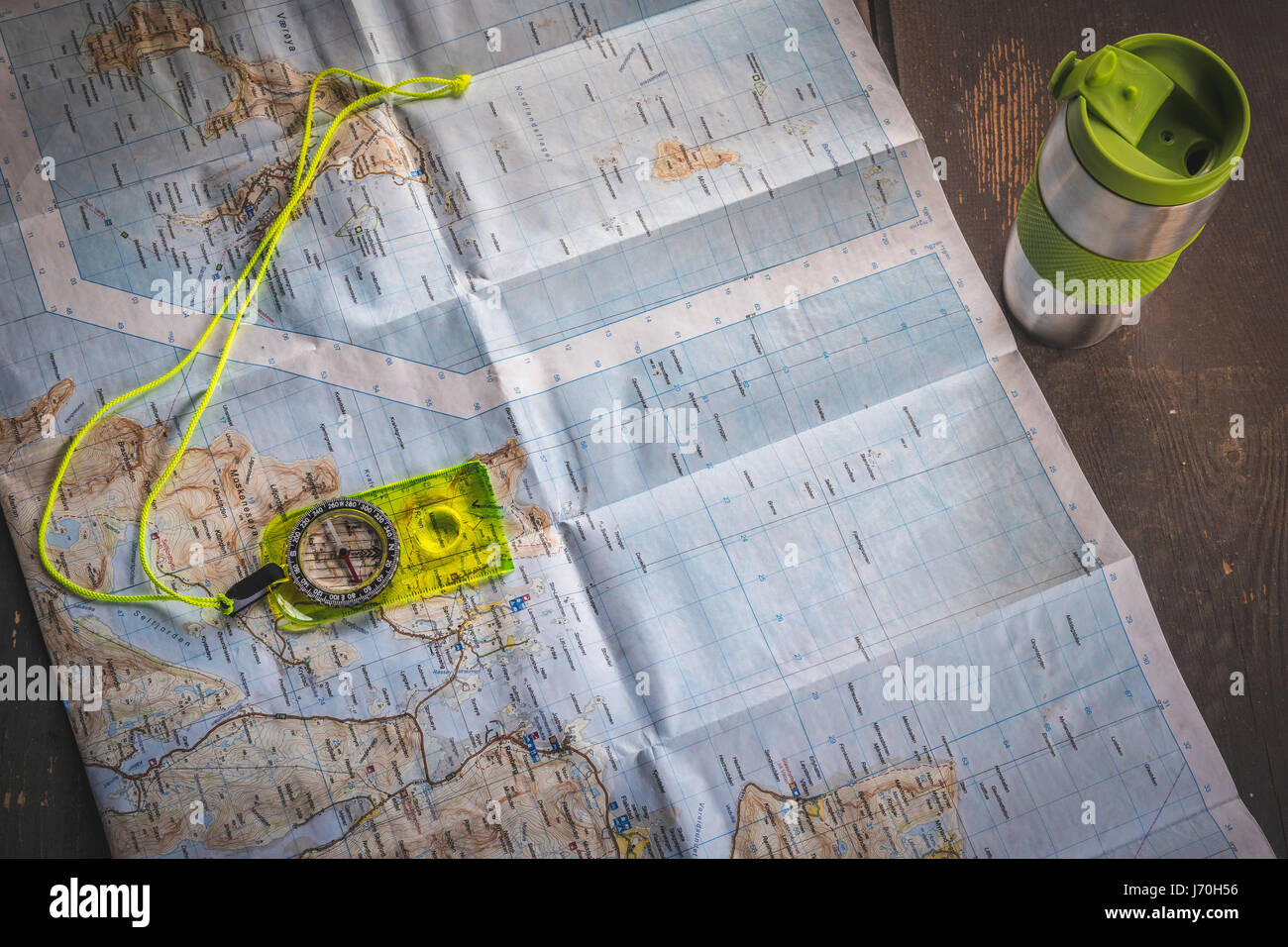 Fluorescent yellow compass lying on map of Lofoten islands, Norway on wooden table next to silver thermal mug - Stock Image