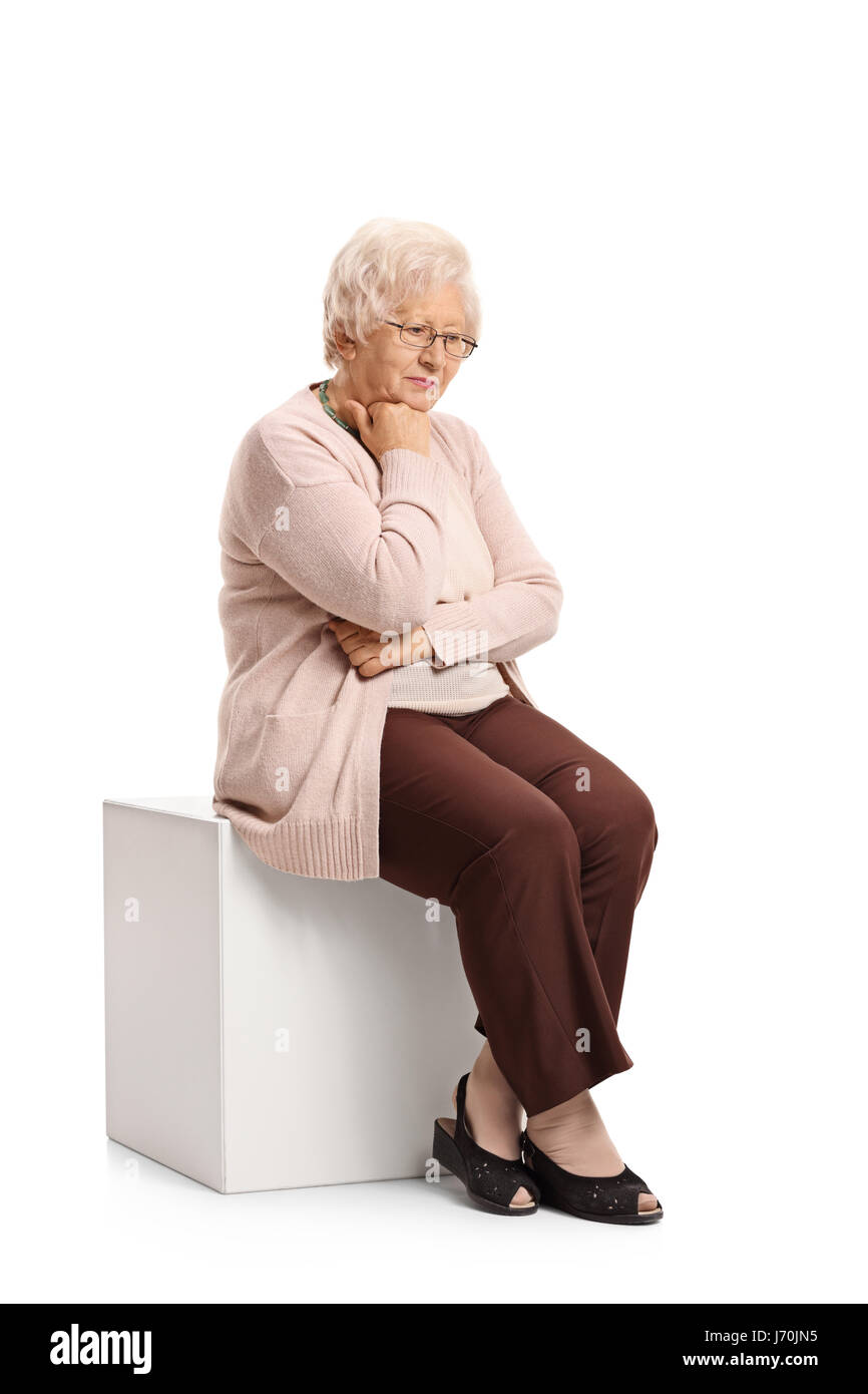 Sad mature woman sitting on a cube isolated on white background - Stock Image