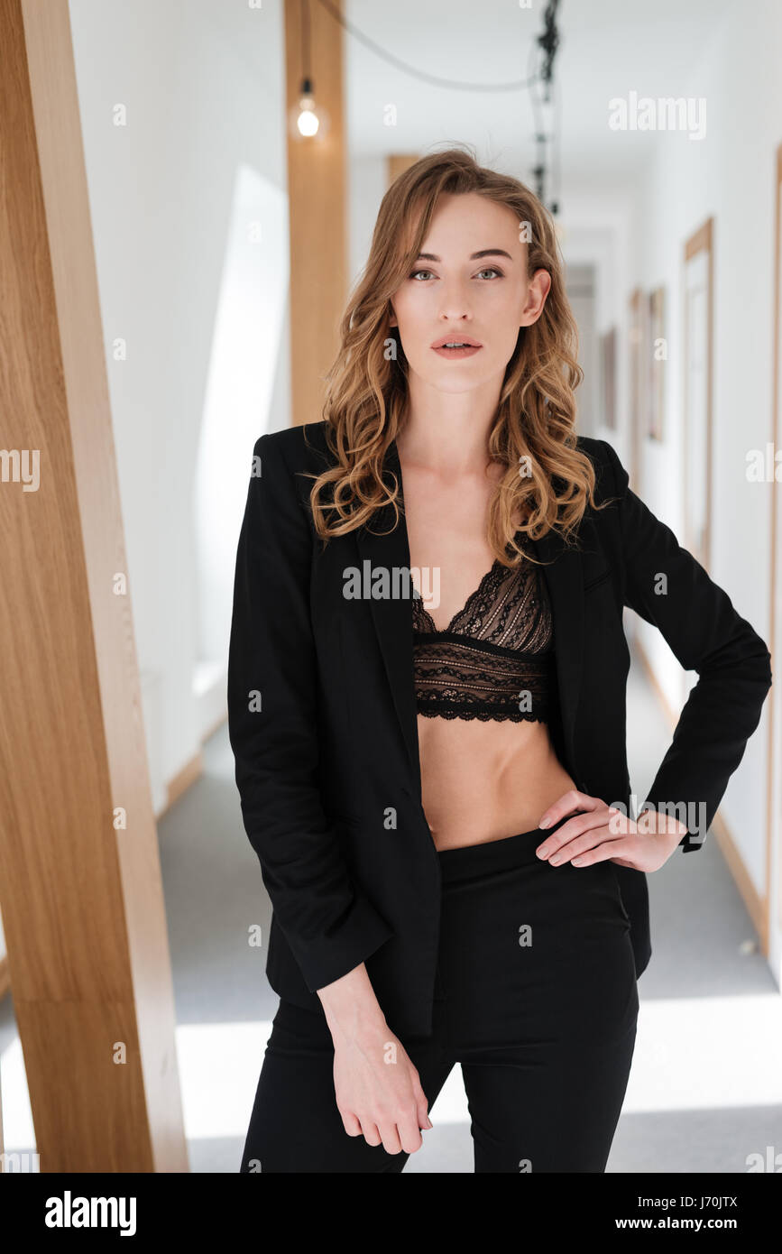 Verical image of pretty woman in suit and bra without shirt posing in apartment - Stock Image