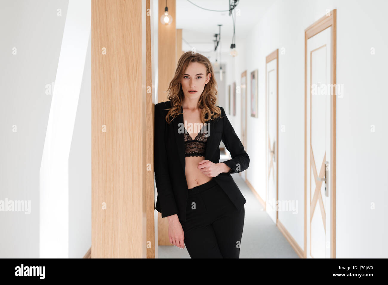 Pretty woman in suit and bra posing in apartmant while holding arm at hip and looking at the camera - Stock Image