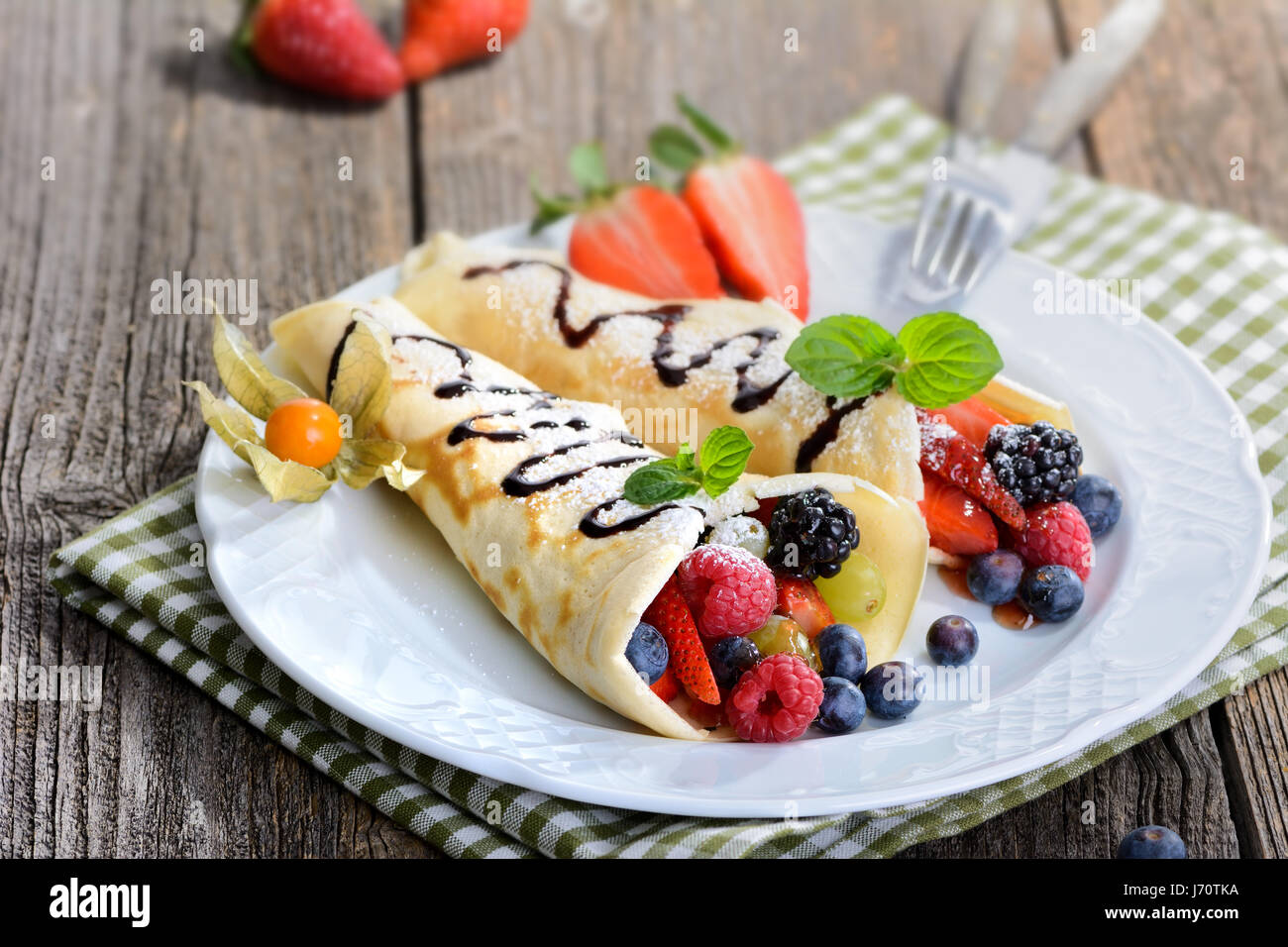 Two homemade pancakes stuffed with mixed fresh berries - Stock Image