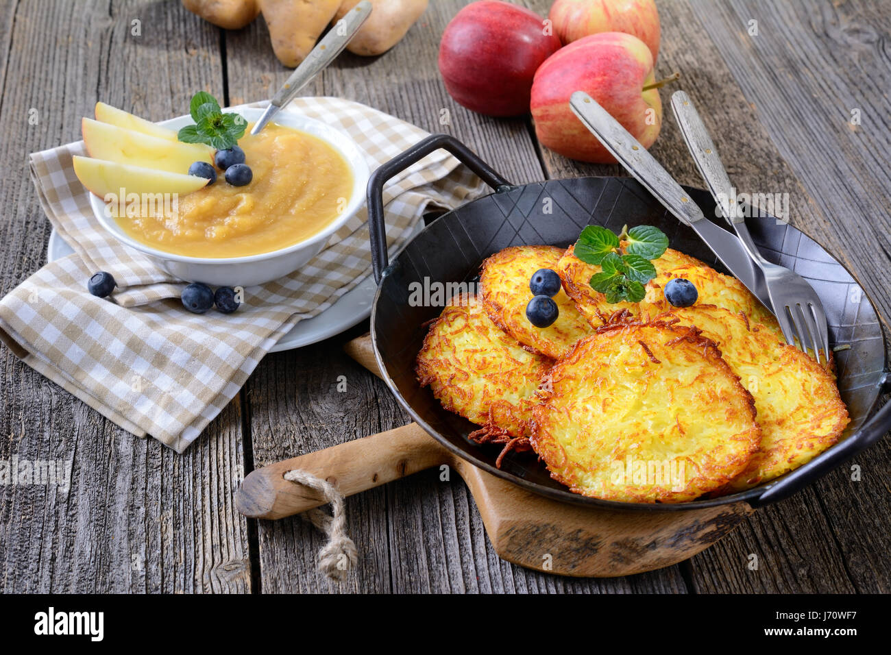 Homemade crispy fried potato pancakes served in an iron frying pan with apple sauce - Stock Image