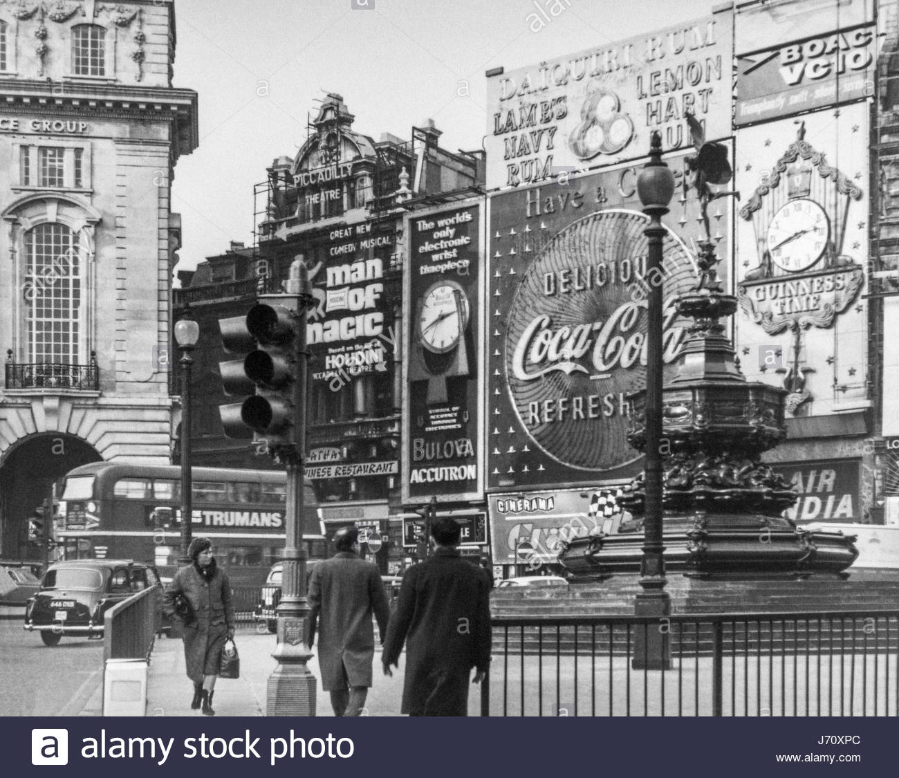 Piccadilly Circus, London, UK,  in winter, with neon adverts and Eros statue, London Routemaster bus and black taxi - Stock Image