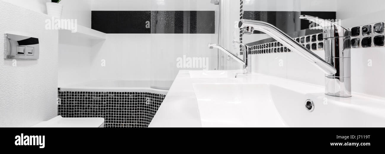 Fancy bathroom taps in black and white classical interior, panorama ...