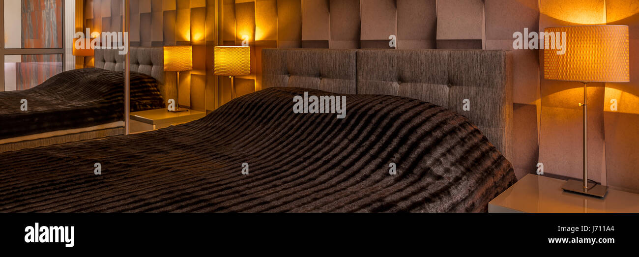 Modern designed bedroom with creative brown 3D wallpaper and big bed, panorama - Stock Image