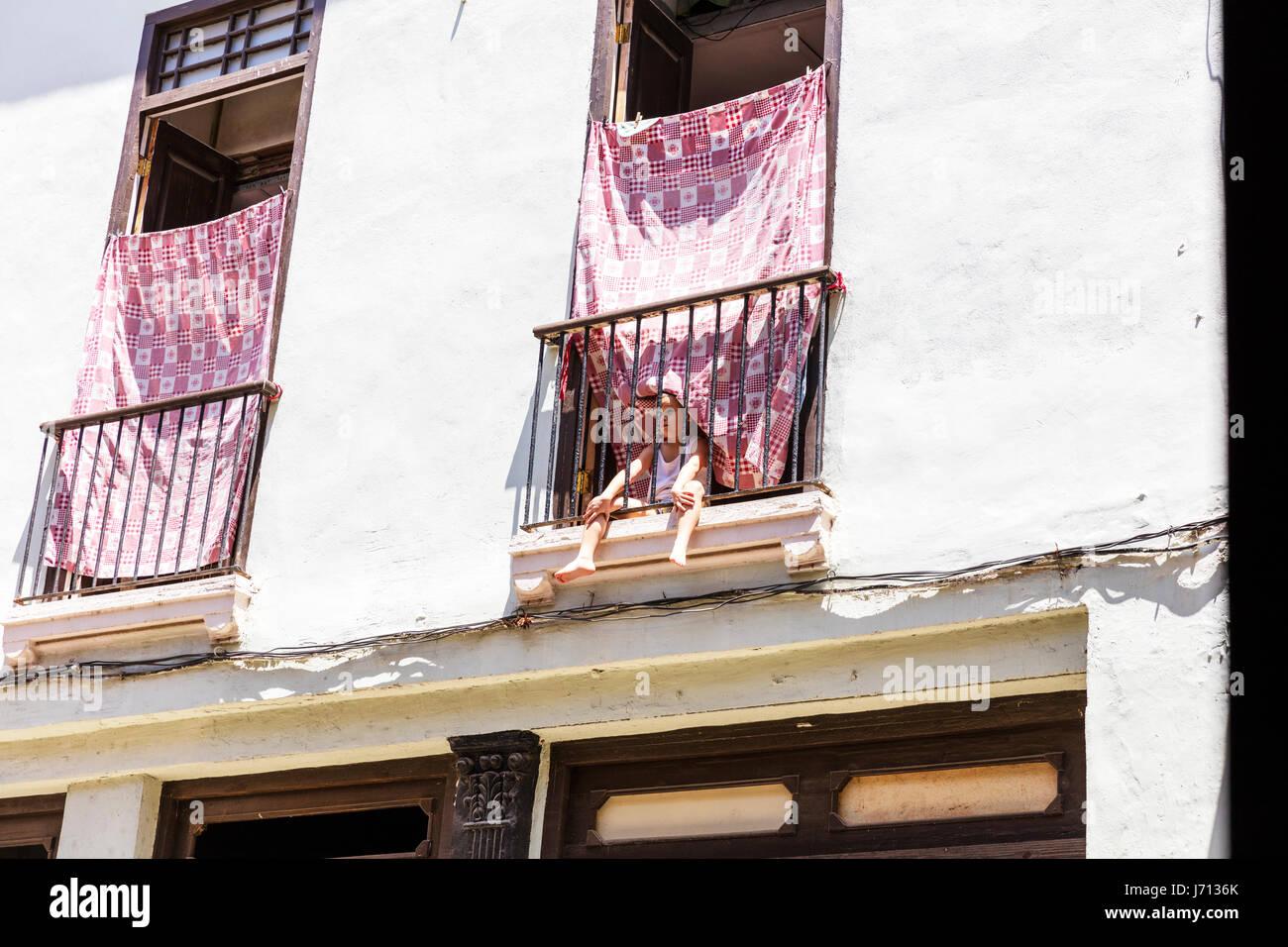 Young boy on hotel balcony alone, young boy looking through railing on hotel balcony, child on balcony, Havana Cuba - Stock Image