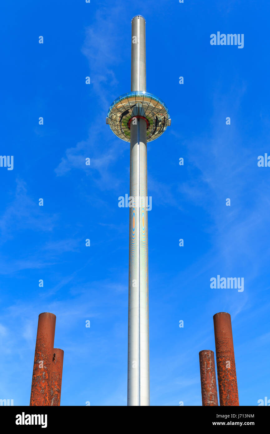 Brighton i360 observation tower on the seafront, with the rusty pier supports of the old West Pier in the foreground. - Stock Image
