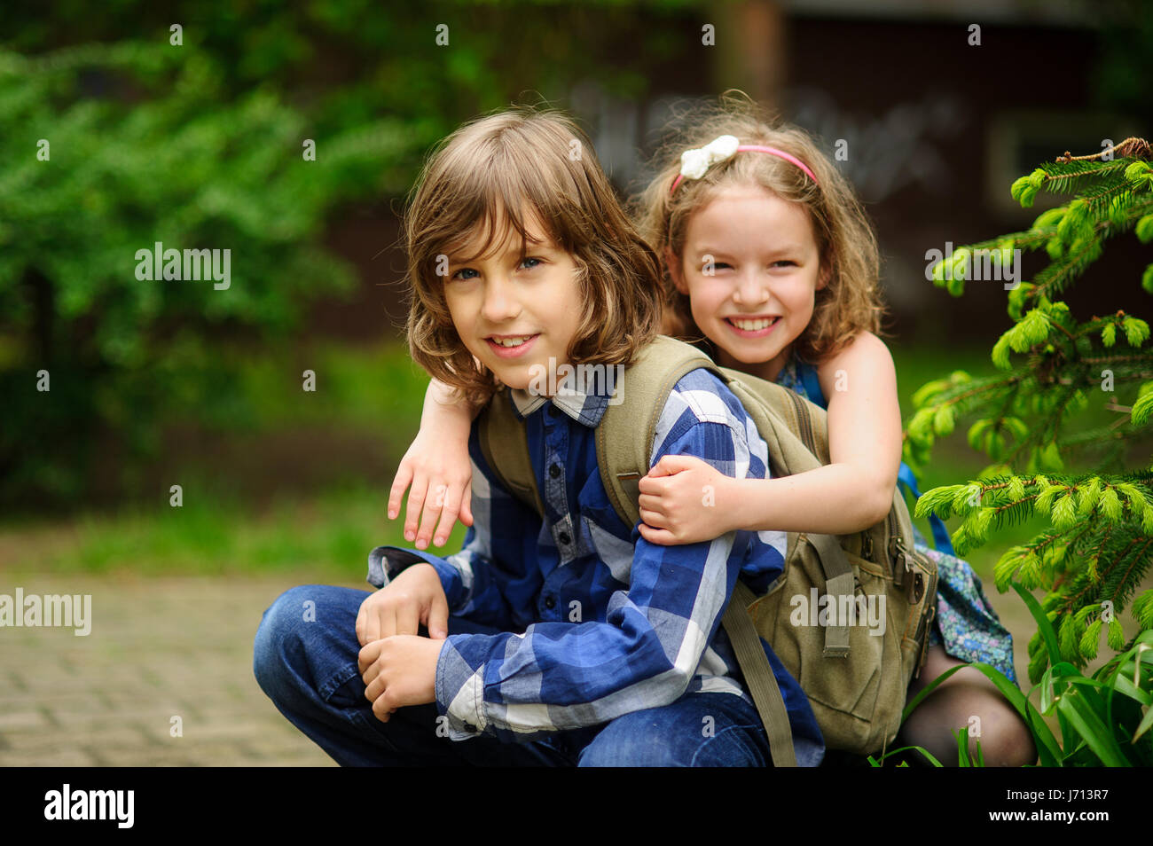 Two children of younger school age, the boy and the girl, squat having embraced. Warm spring day. School students - Stock Image