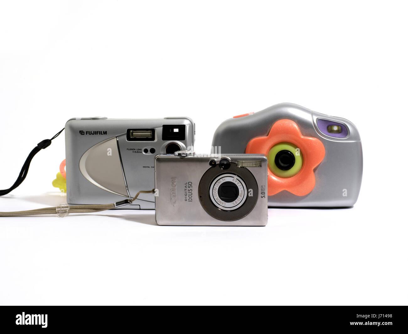 Three Digital Cameras - Fujifilm Finepix 2300, Canon Ixus 50 and Barbie Digital Camera - Stock Image