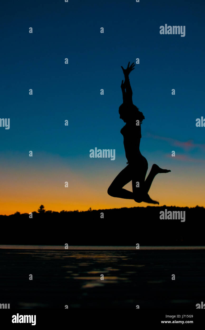 silhouette of a teenage girl jumping off a dock into a lake at sunset Stock Photo